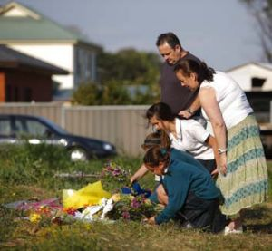 United in grief ... friends of the Dunn family lay flowers at the scene yesterday.