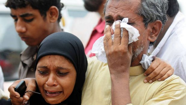 Grief … relatives of workers killed in Karachi.