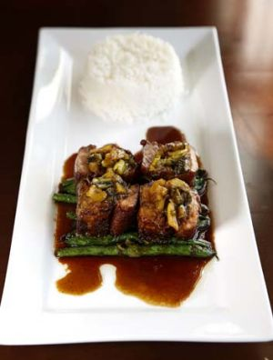 Pork ribs with caramelized sweat and sour soy glaze with round beans and mustard leaves.