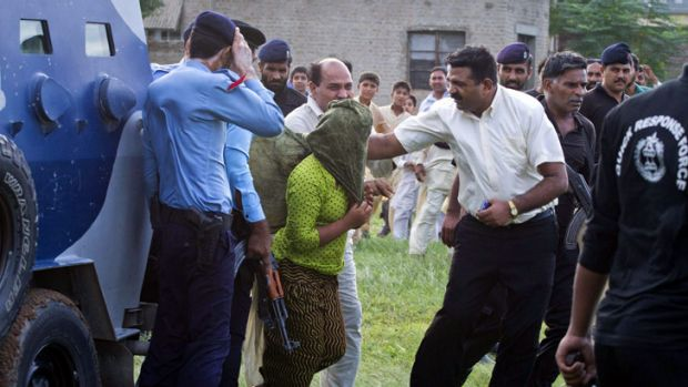 Heavily armed security officials rush Rimsha Masih, a Christian girl accused of blasphemy, to a military helicopter to ...