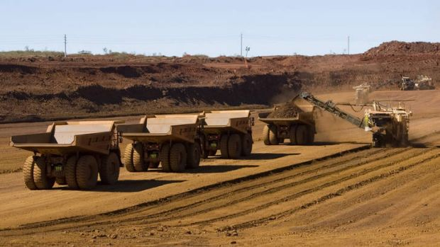 Haul trucks wait to be loaded with iron ore at a Fortescue Metals Group mine in West Australia's Pilbara region.
