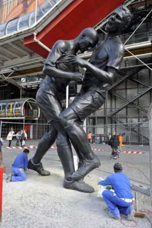 Employees work in Paris near a bronze sculpture by Algerian artist Adel Abdessemed, immortalising the headbutt given by ...