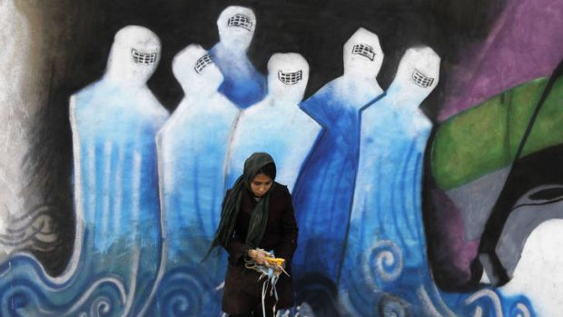 An Afghan woman, Shamsia Hassani, removes rubbish in front of her graffiti in an industrial park in Kabul December 19, ...