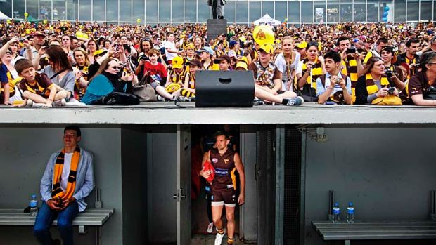 A crowd of about 8000 cram in for the Hawks training session; a fan enjoys the moment as Luke Hodge leads the players out.