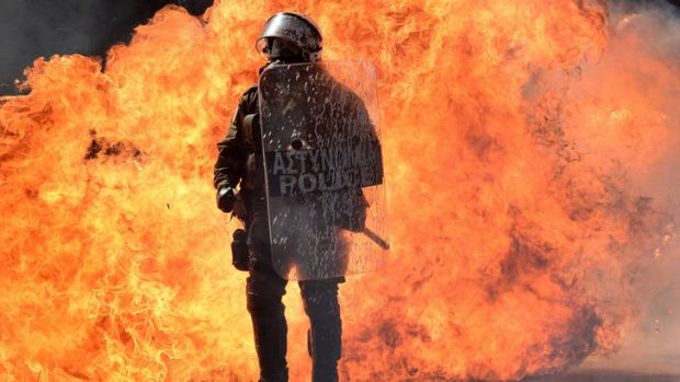 Up in flames ... burning firebombs form a backdrop to a riot officer during a demonstration in Athens on Wednesday.