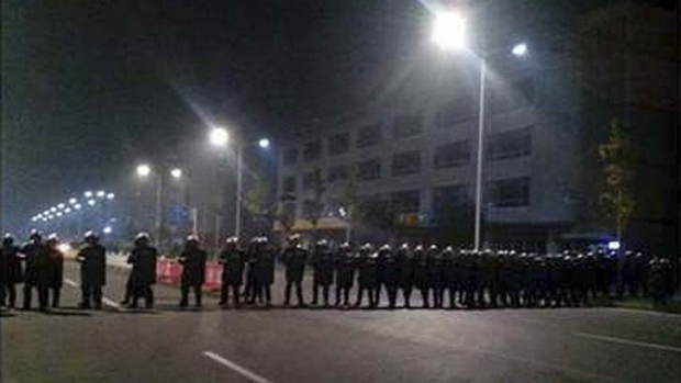 Police in anti-riot suits cordon off a road near Foxconn's plant in Taiyuan.