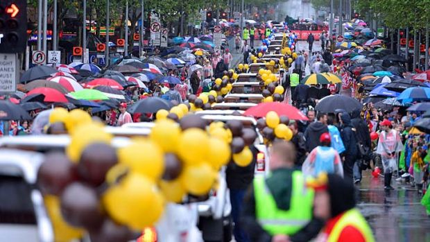 Thousands brave wet conditions for the annual Grand Final parade through Melbourne streets.