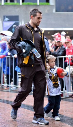 True leader: Luke Hodge with his son Cooper in yesterday's parade in the city.