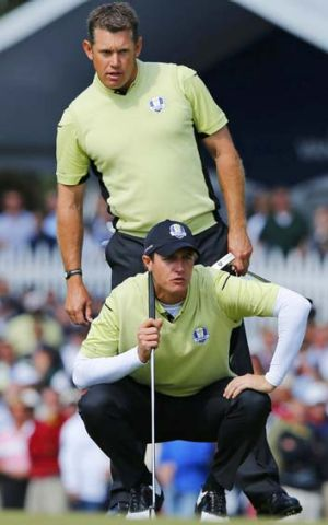 Team Europe golfers Nicolas Colsaerts of Belgium and Lee Westwood of England (top) size up a putt.