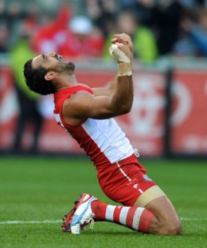 Twice as sweet … Sydney stalwart Adam Goodes becomes a dual premiership medal winner and drops to his knees after ...