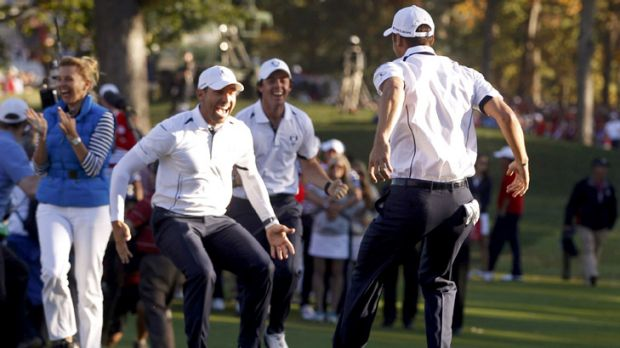 Germany's Martin Kaymer celebrates with European teammates Sergio Garcia and Rory McIlroy after his winning putt.