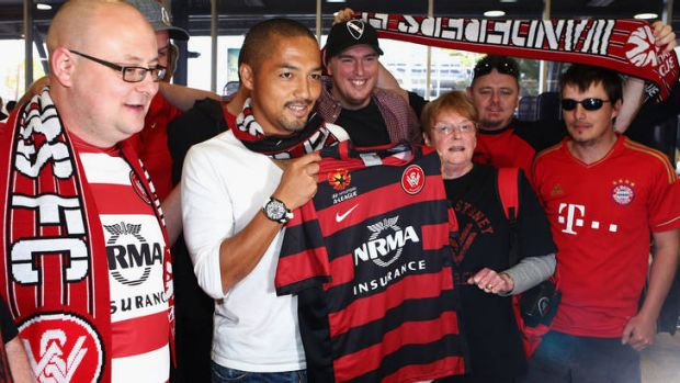 Shinji Ono holds a Western Sydney Wanderers playing shirt as he poses with supporters after his arrival at Sydney ...