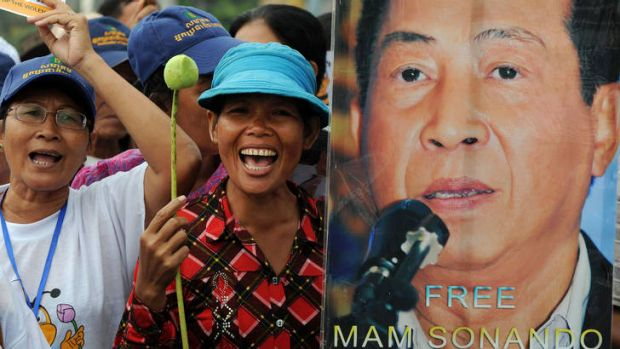 Cambodian protesters shout slogans next to a portrait of Mam Sonando on Monday.