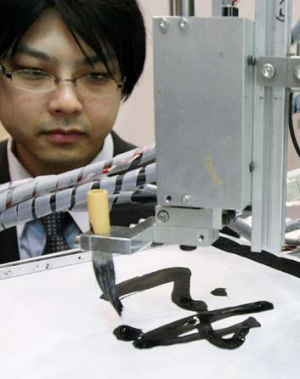Keio University associate professor Seiichiro Katsura demonstrates a robot that can mimic the exact brush strokes of ...