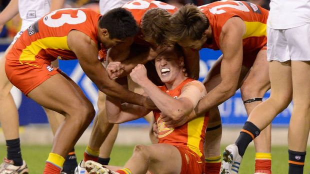 Josh Caddy of the Suns celebrates a goal with team mates.