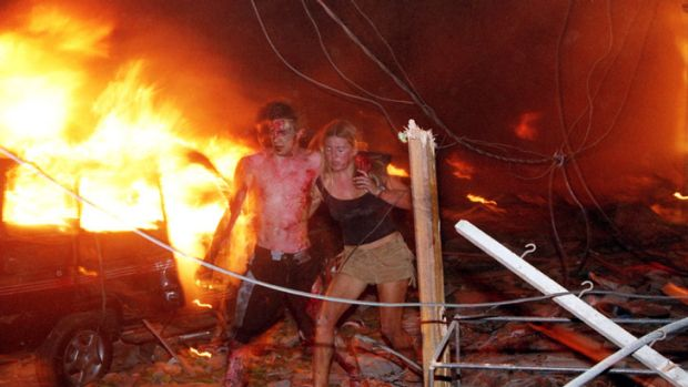 The iconic image of Hanabeth Luke assisting Tom Singer through the flames of the Sari Club in Bali.