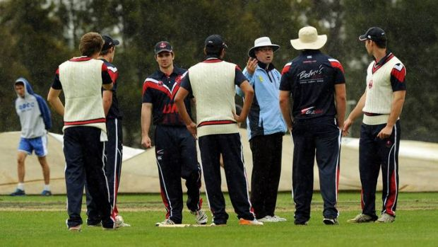 Eastlake player's in discussion with the umpire after the cover's where called for during yesterday's rained out clash.