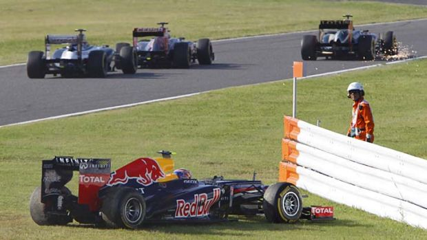 Sparks will fly ... Red Bull driver Mark Webber sits in the grass after colliding with the Lotus of Kimi Raikkonen, top ...
