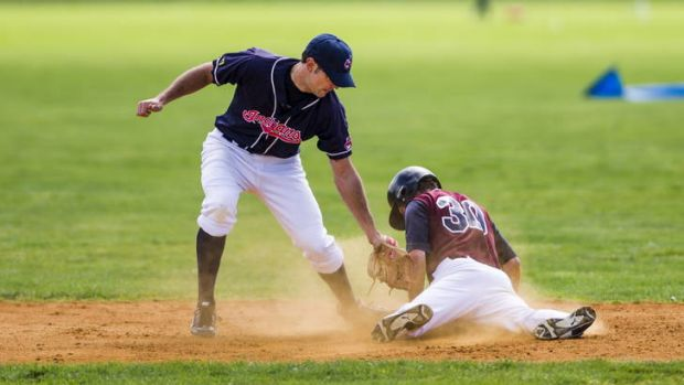 Woden's Julian Pozza dives for second base in front of Weston Creek's Cable Dohnt.