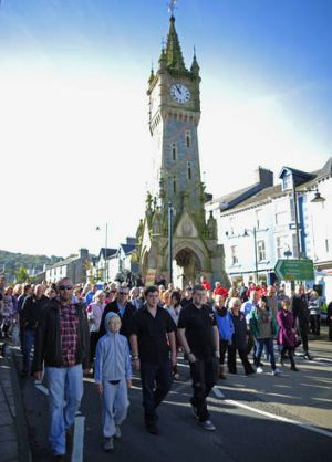 Resilience ... hundreds of Machynlleth residents walk together to St Peter's Church for yesterday's service.