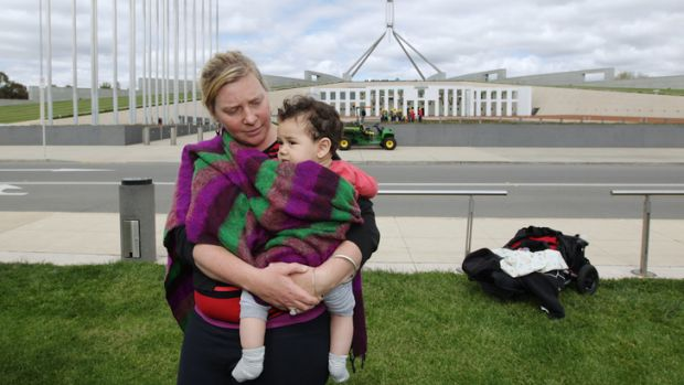 A single mum protests outside Parliament House.