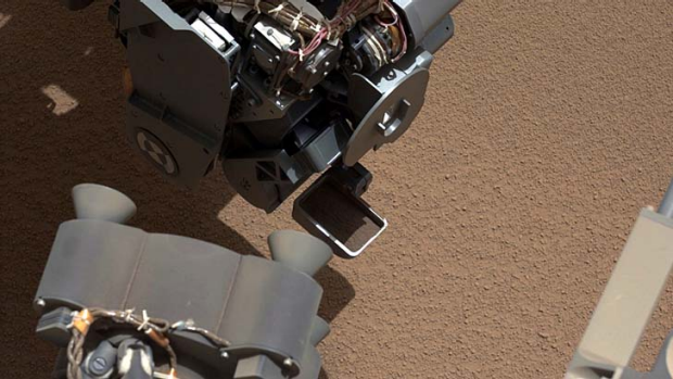 Curious ... NASA's Mars rover shows a scoop full of sand and dust lifted by the rover's first use of the scoop on its ...