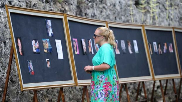 Emotional families and friends viewing a picture board of the victims of the Bali bombing attack at the official ...