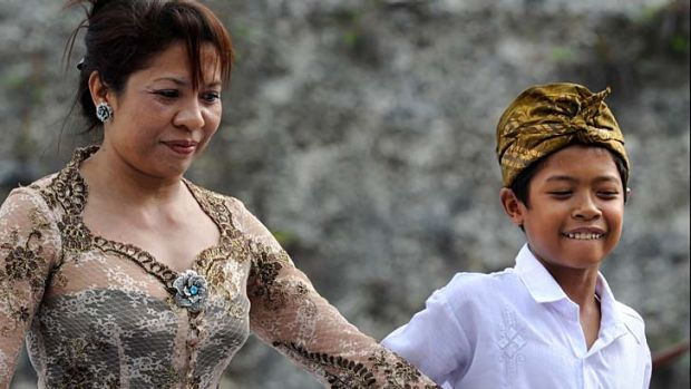 Made Bagus Arya Dana leaves the stage with his mother after reading his poem.