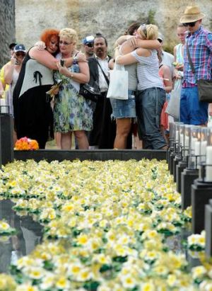 Lest we forget: Emotional family and friends place floral tributes in the pool of remembrance at the memorial service in ...