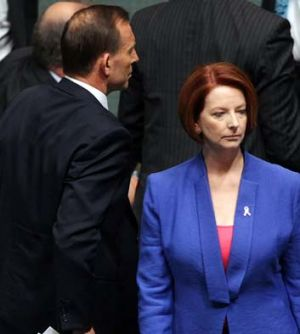 Ships passing ... Tony Abbott and Julia Gillard cross paths in the Parliament.