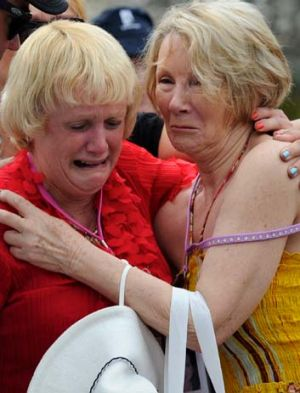A little solace … Pauline Whitton, left, and Lynn Muller comfort each other at the memorial.