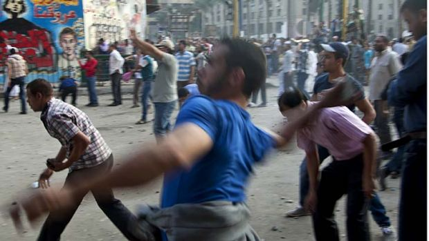 Throwing stones ... protesters in Cairo's Tahrir Square.