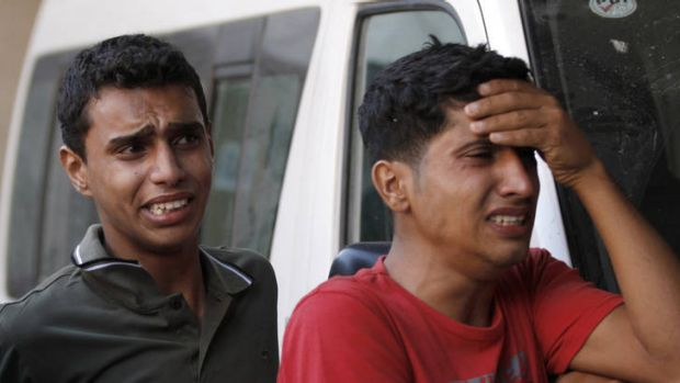 Retaliation ... relatives of the two Palestinian militants killed in Sunday's air strike mourn outside a hospital in Gaza.