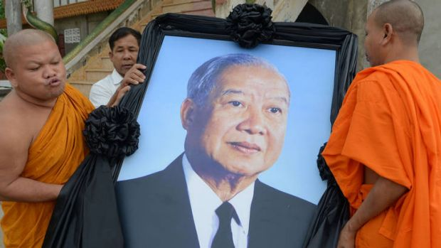 Mourning ... Buddhist monks carry a portrait of Norodom Sihanouk in preparation for the return of his body to Phnom Penh.
