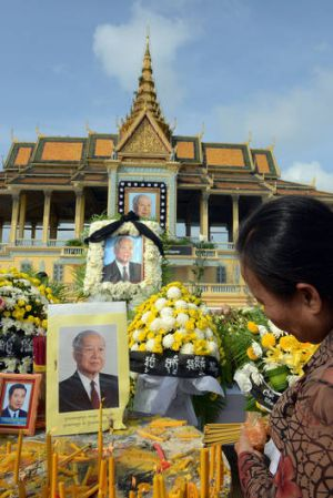 Reverence ... a Cambodian woman burns incense in front of Sihanouk's image at the royal palace in Phnom Penh.