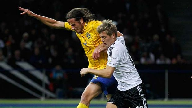 Toni Kroos (right) of Germany and Jonas Olsson of Sweden battle for the ball.
