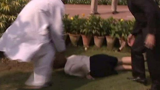 Tripping up ... Ms Gillard tumbles near the Gandhi memorial in Delhi.