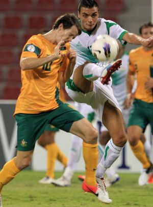Taking one for the team ... Robbie Kruse of Australia competes with Ahmed Yaseen Gheni of Iraq.