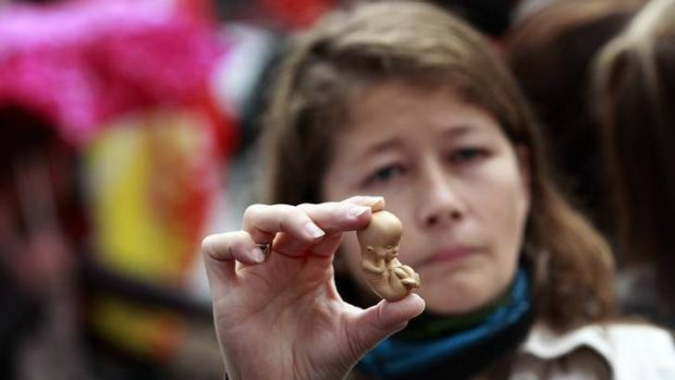 Cultural conflict ... a pro-life campaigner holds up a model of a 12-week-old embryo outside the Marie Stopes clinic.