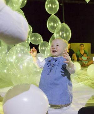 A baby interacts with balloons during a performance of <i>How High the Sky</i>.