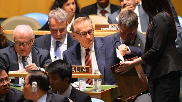 A campaign on the global hustings ... the Foreign Minister, Bob Carr, centre, places his vote in the ballot box with the ...