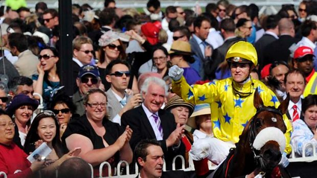 Top of the class: Craig Williams returns to scale in triumph on Caulfield Cup winner Dunaden yesterday.