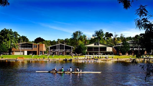 A crew rows past the boatsheds opposite Federation Square yesterday.