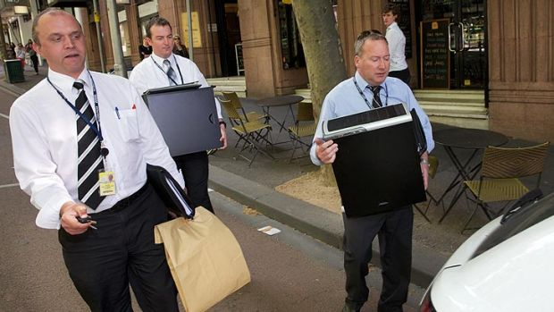 Detectives remove items after the raid on the city offices.