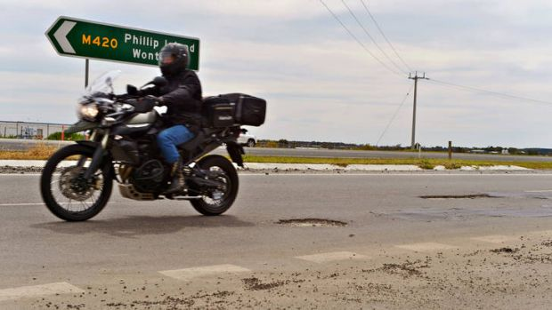 Danger: A rider negotiates potholes on the Bass Highway. Thousands of motorcyclists will travel along the route to ...