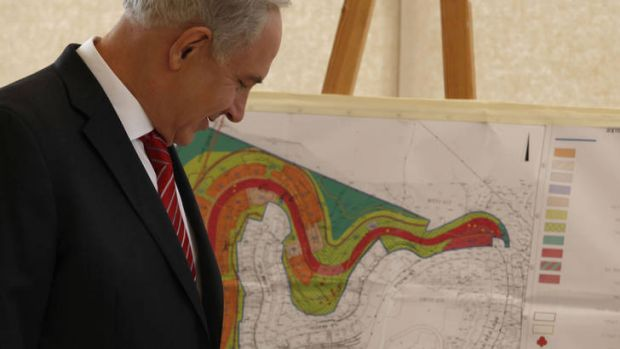 Facts on the ground ... Mr Netanyahu looks at a map of the area where Israel plans to build 800 units in Gilo.