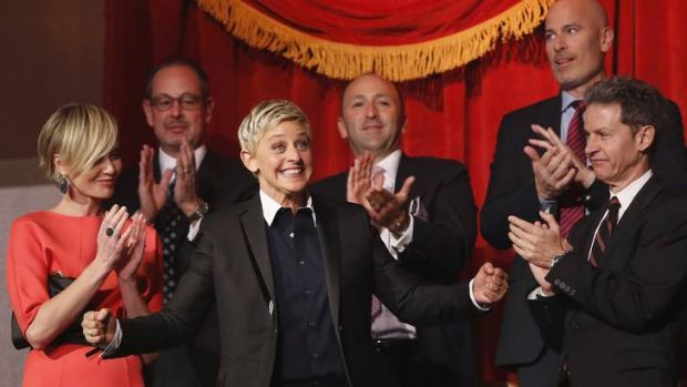 Ellen DeGeneres smiles as her family and friends, including wife Portia de Rossi (left), applaud her entrance at the ...