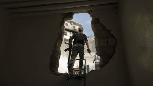 Chink of light ... a Free Syria Army fighter walks through a hole in the wall during fighting in Aleppo.