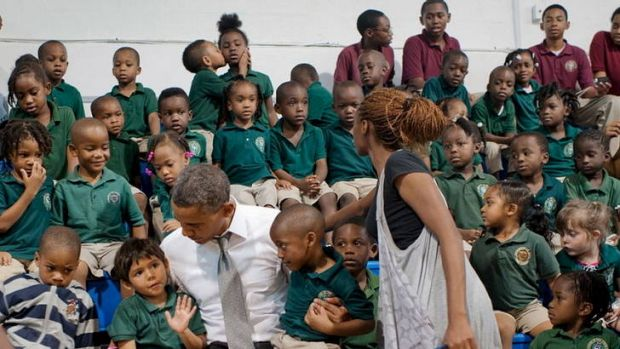 Otherwise engaged ... a boy kisses a girl while Barack Obama visits a school in Florida.