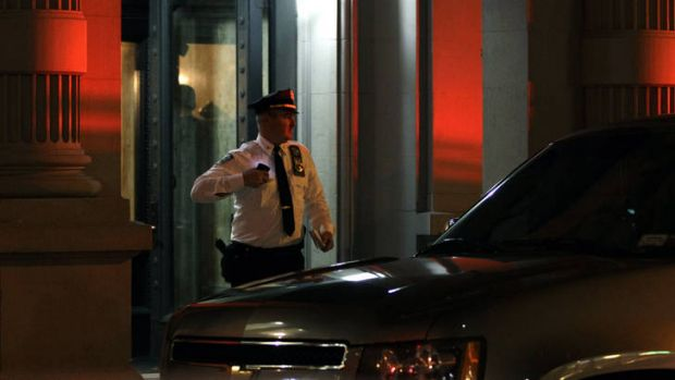 A police officer leaves the luxury Manhattan apartment building where the family lived.